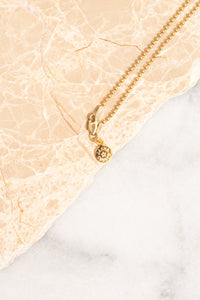 closeup of gold ball chain necklace with nametag