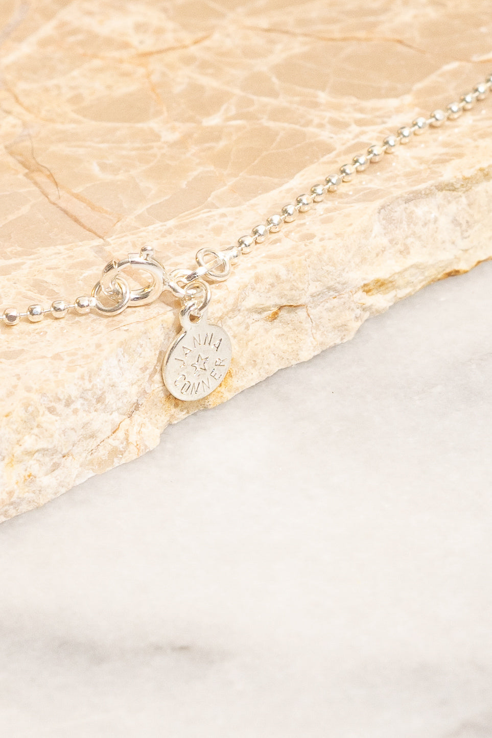 silver ball chain necklace closeup with nametag