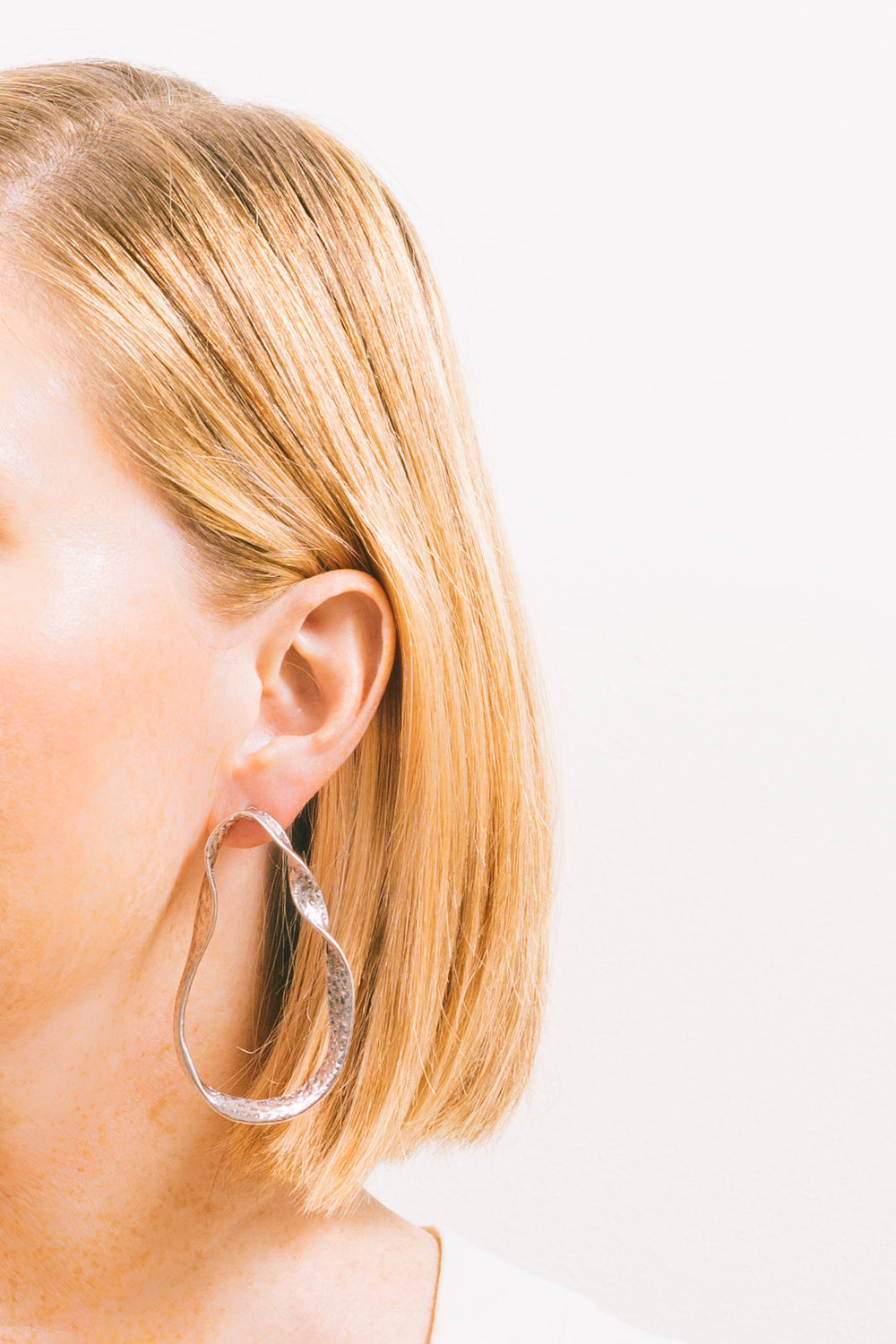 twisted metal sculptural earrings on model