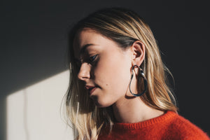 twisted metal earrings on model dramatic shadow lighting janna conner