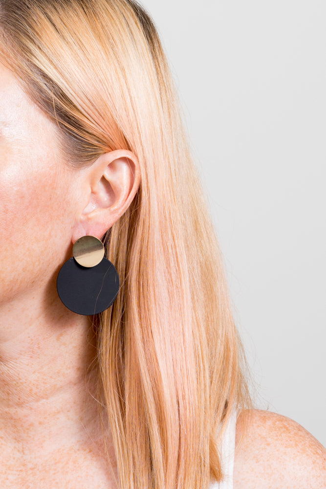 black disc earrings with gold accents on model