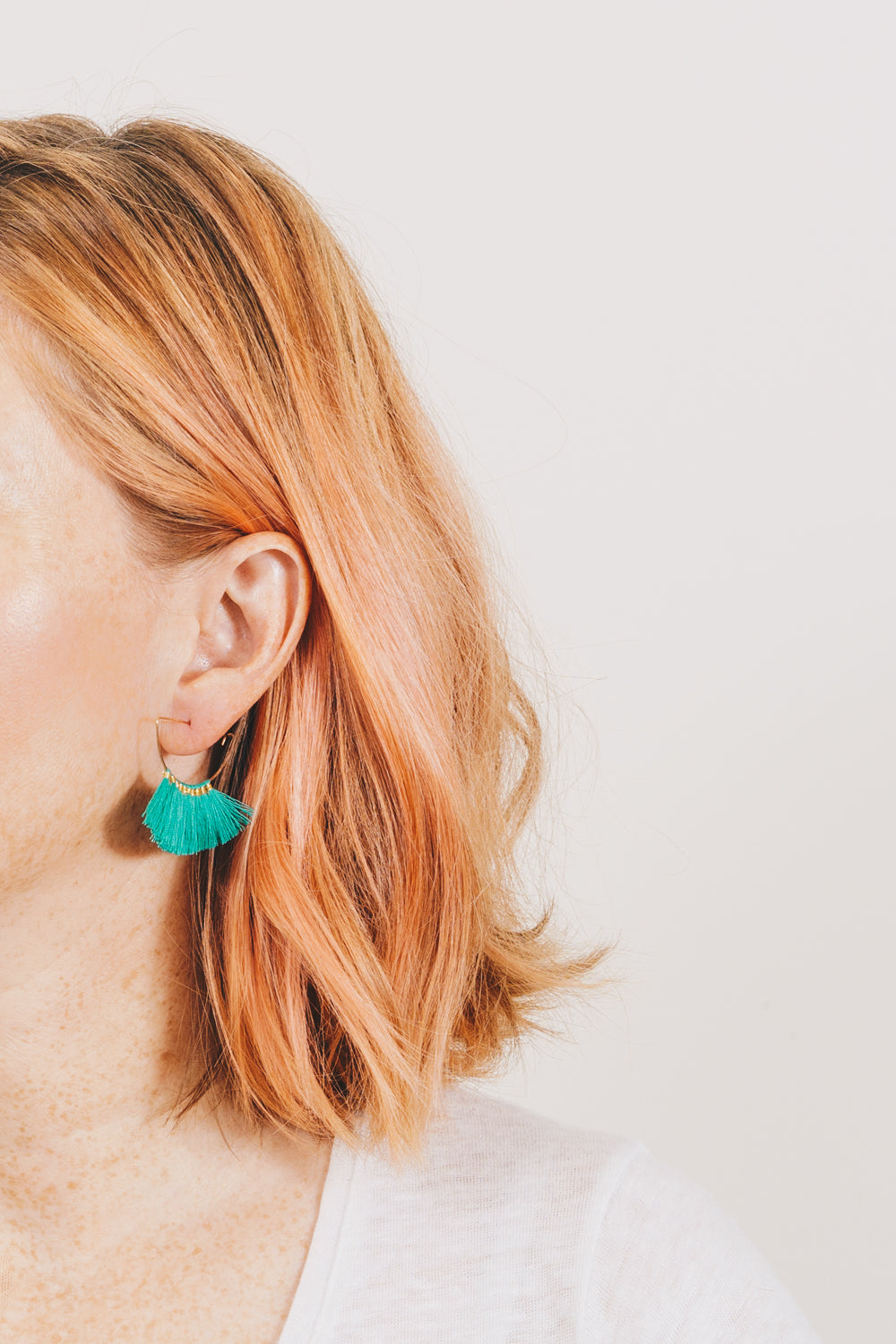 green cotton fringe tassel hoop earrings on model