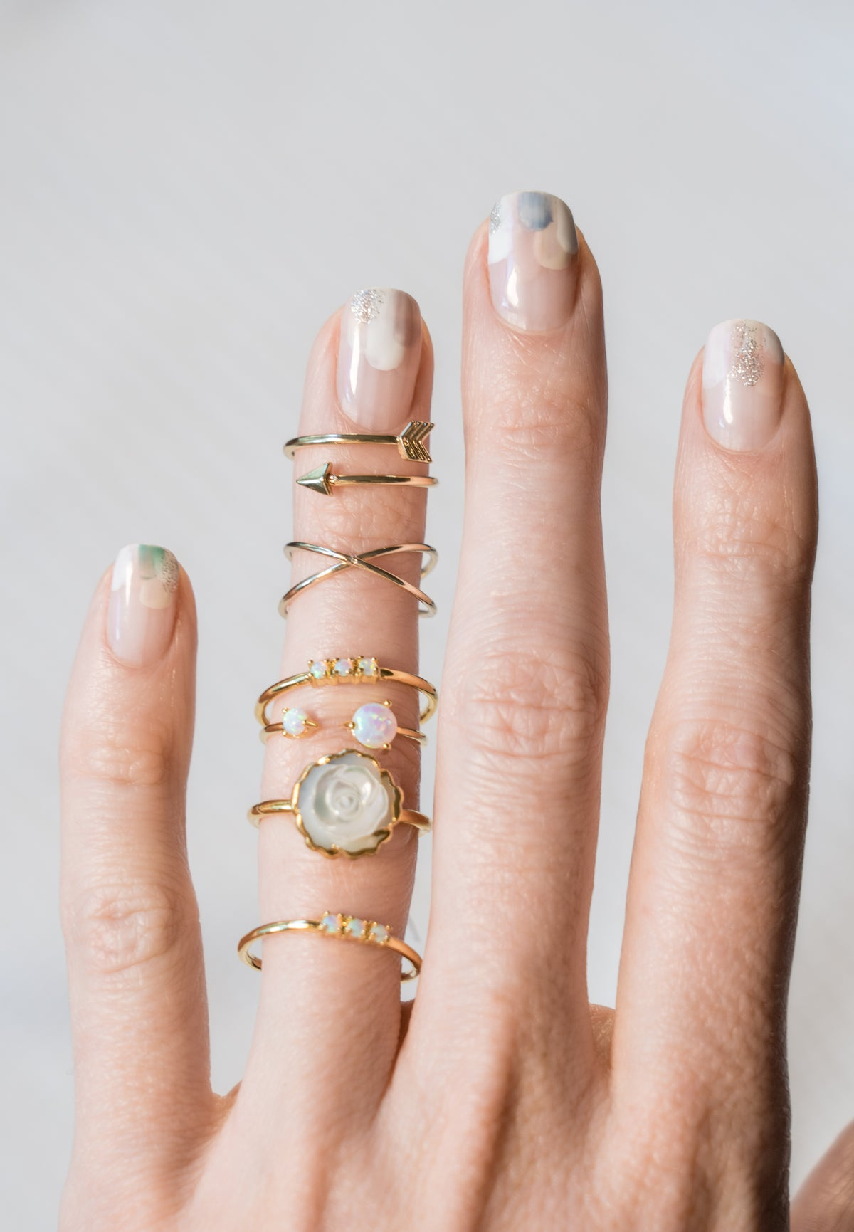 mother of pearl rosette ring and opal ring stacks on model hand