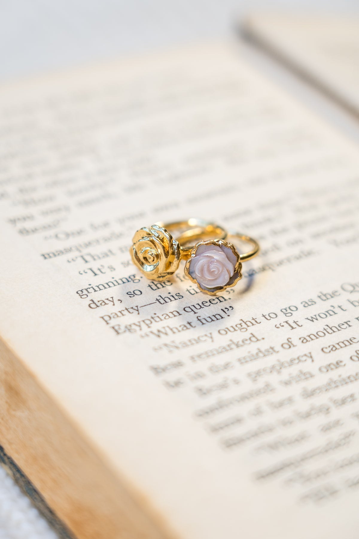 janna Conner pink mother of pearl and gold plated rosette rings on book
