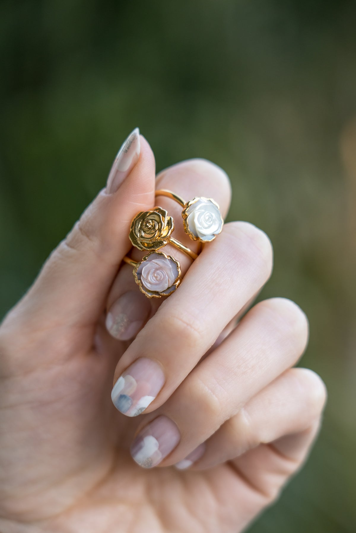 janna Conner pink mother of pearl and gold rosette ring stacks in model hand with nail art mani