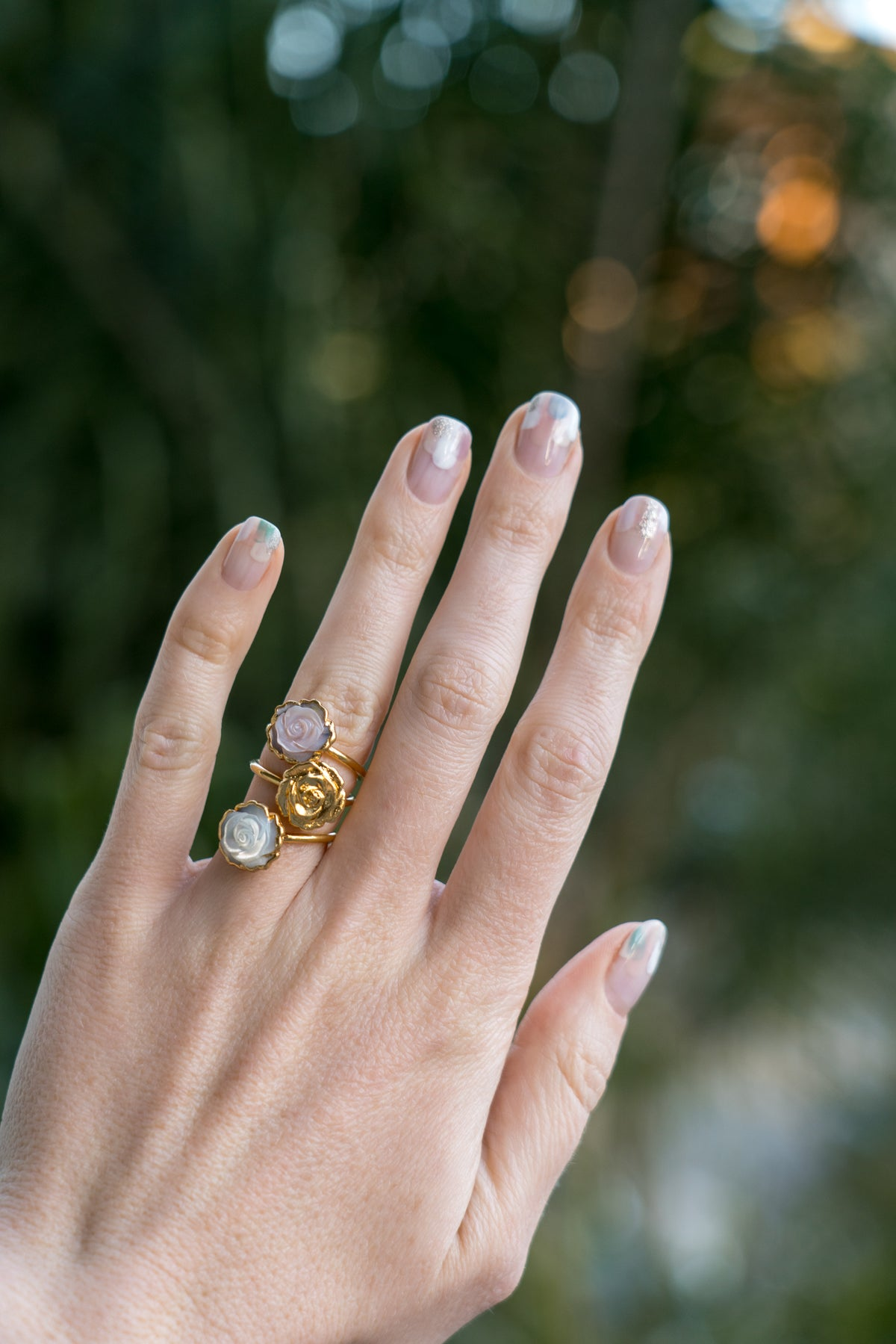 janna Conner pink mother of pearl and gold plated rosette ring stacks on model hand  with nail art mani