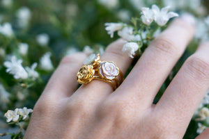 janna Conner jewelry mother of pearl and gold plate rosette ring stacks on model hand in white flowers