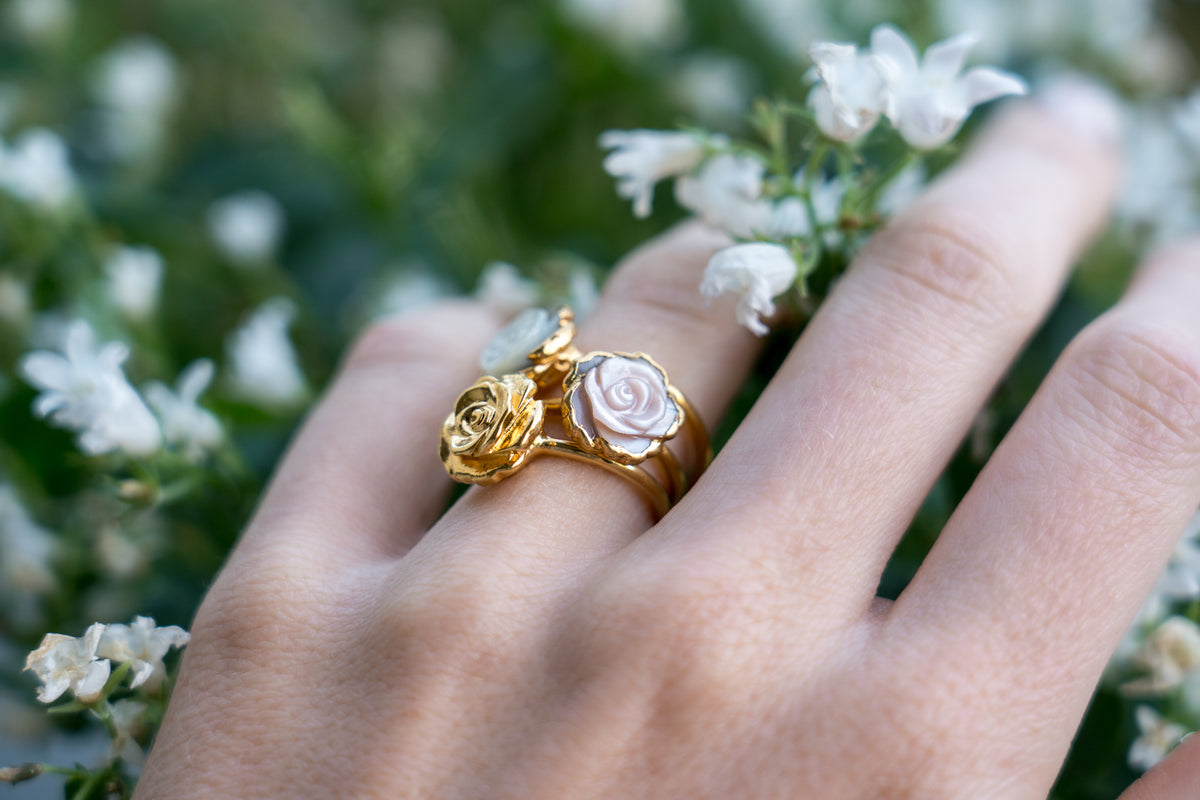 janna Conner jewelry pink mother of pearl and gold plate rosette ring stacks on model hand with white flowers