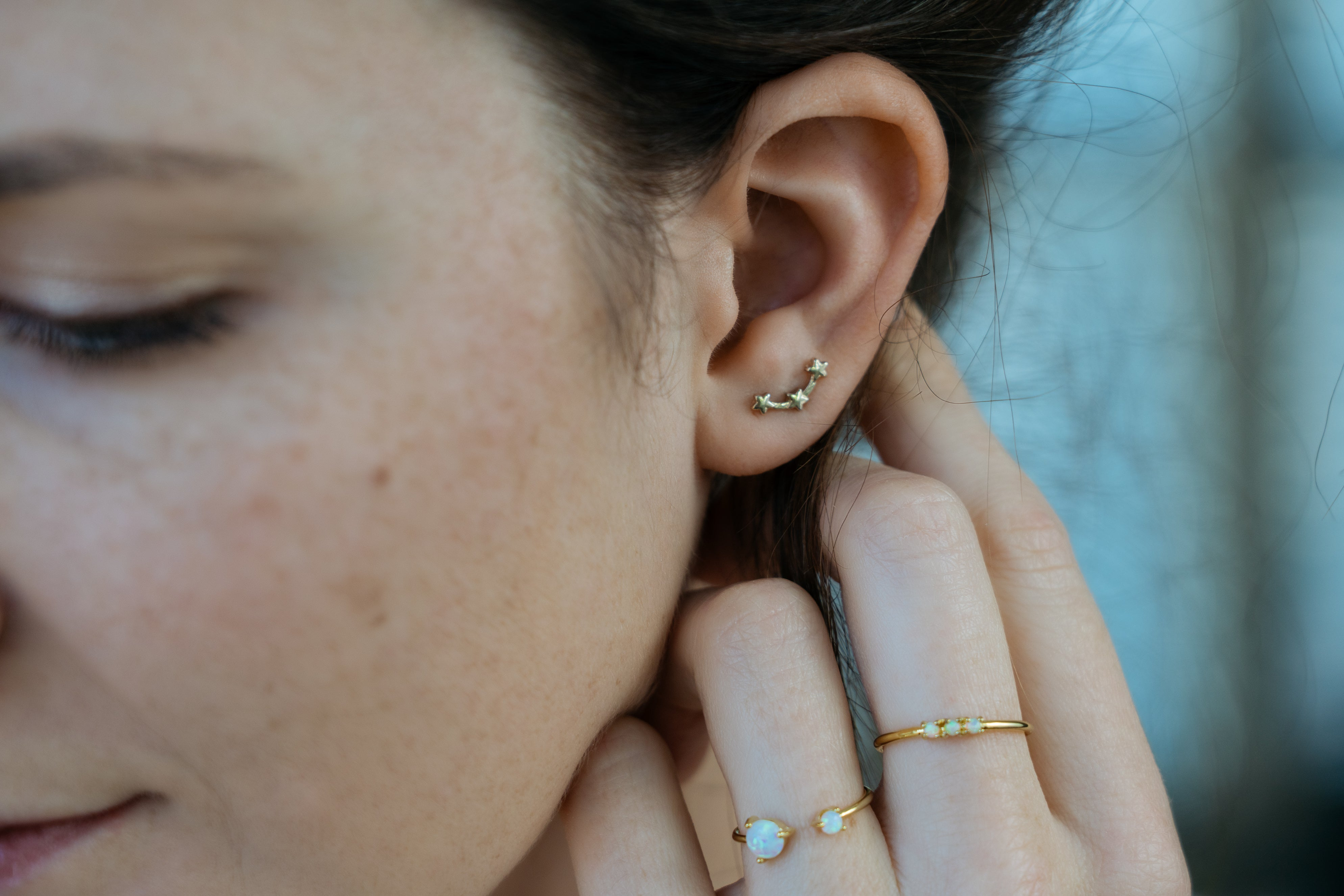 gold star ear climbers on model closeup and opal rings