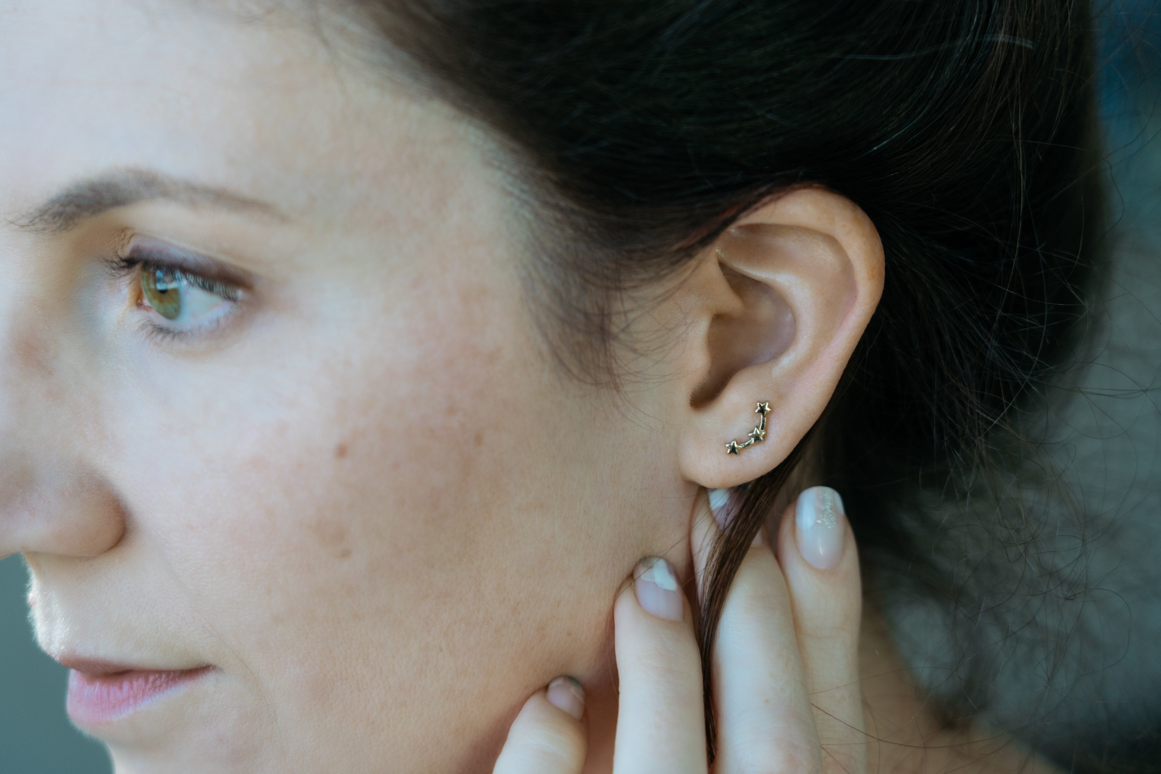 girl touching ear with gold star ear climbers