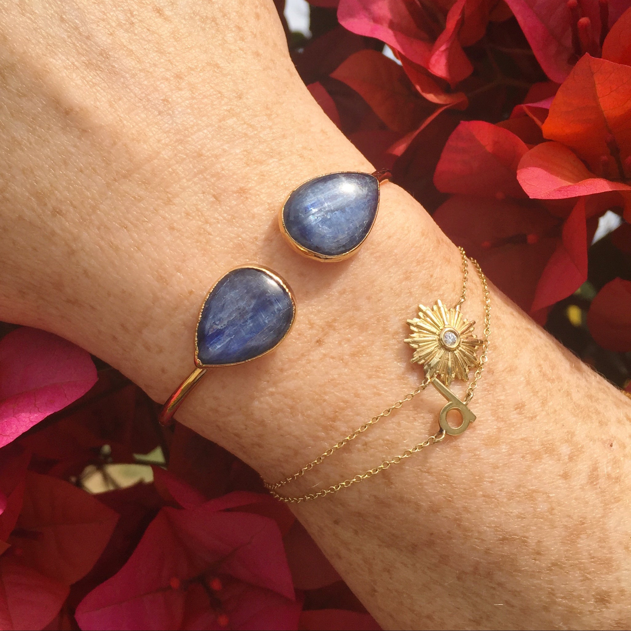 model wrist with gold starburst bracelet, d initial bracelet and kyanite cuff with bougainvillea janna Conner