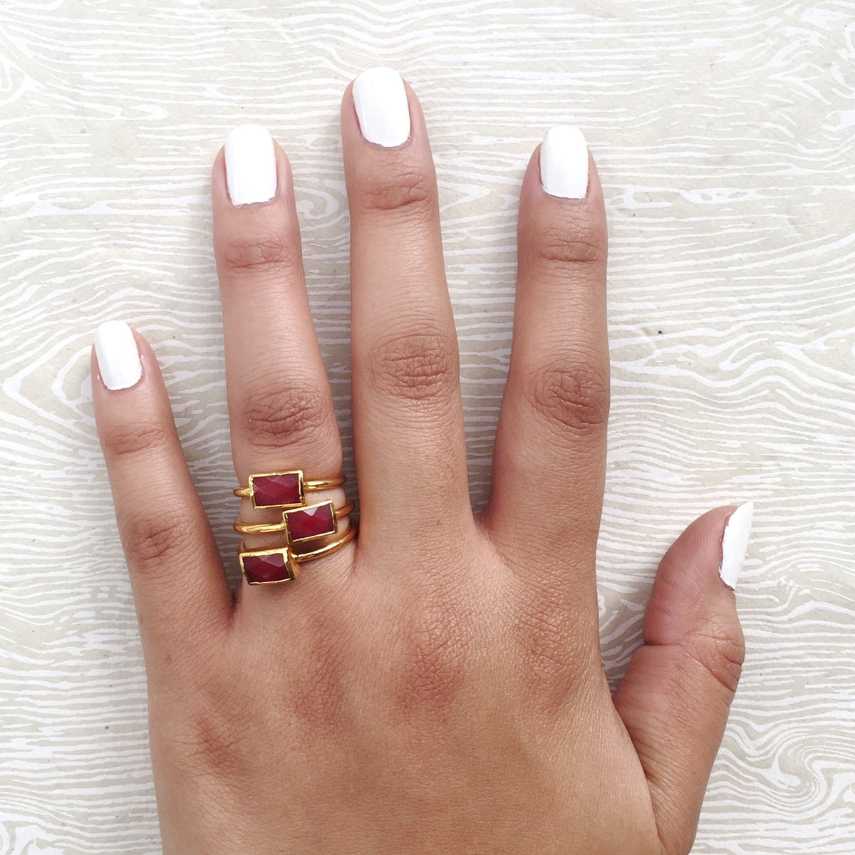 red rectangular stacking rings on hand