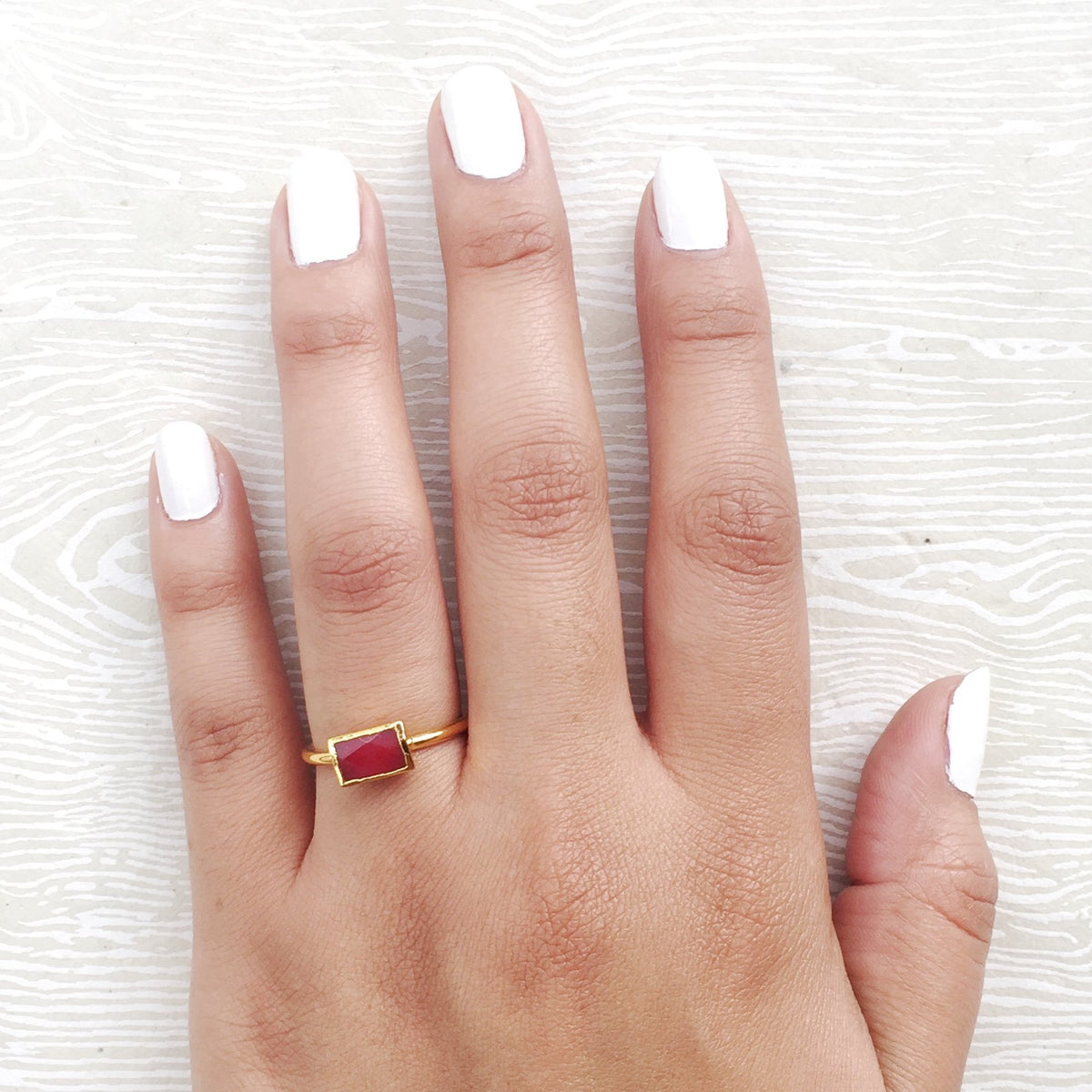 red semi precious stacking rings on hand