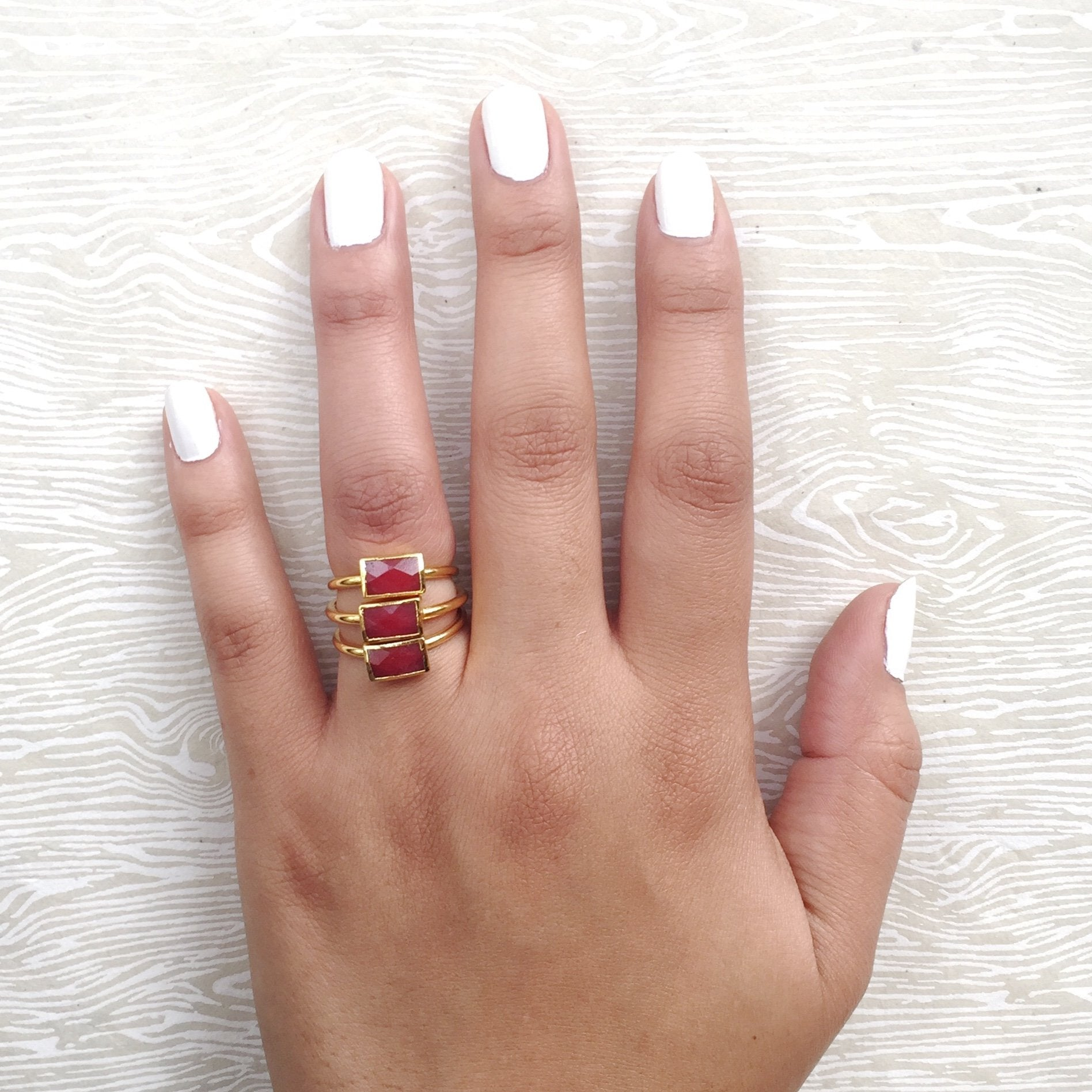 red semi precious stacking rings on hand with three stacked