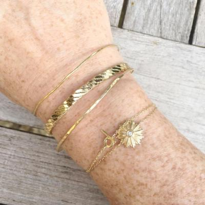 gold stacking bracelets on model arm gold d initial bracelet, diamond  starburst bracelet and gold cuff and bangles by janna conner