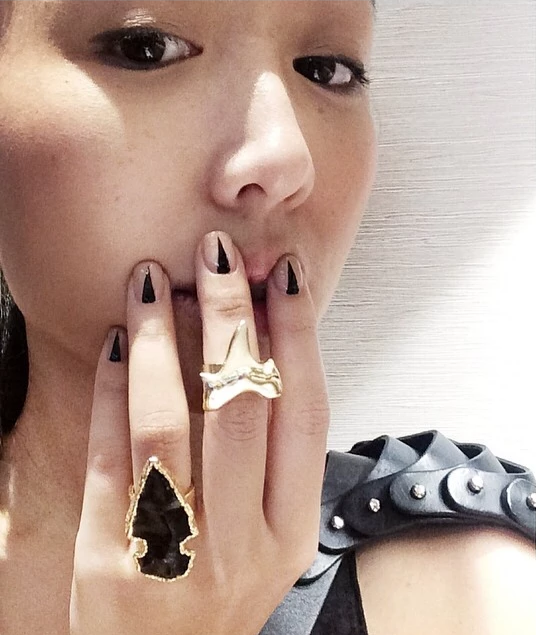 obsidian arrowhead ring and shark tooth ring on girls hand on mouth