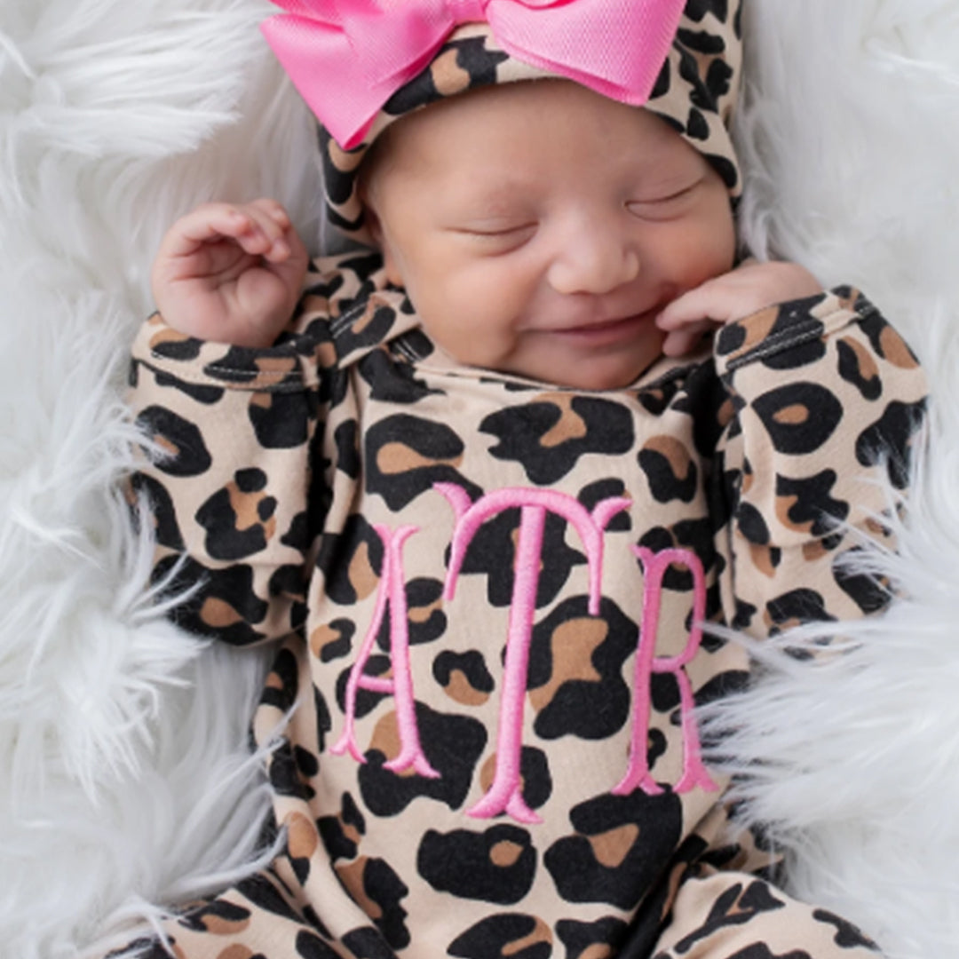 A happy, smiling baby wearing the Junie Grace Personalized Baby Girl Leopard Print Outfit.