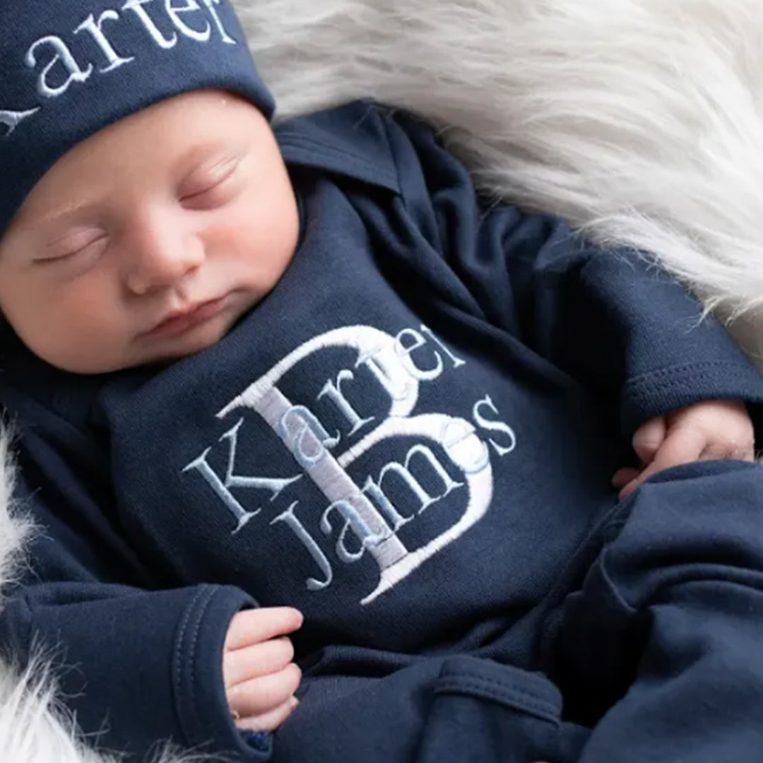A baby boy wearing the super soft personalized Navy Blue Boys Hat & Romper outfit from Junie Grace.