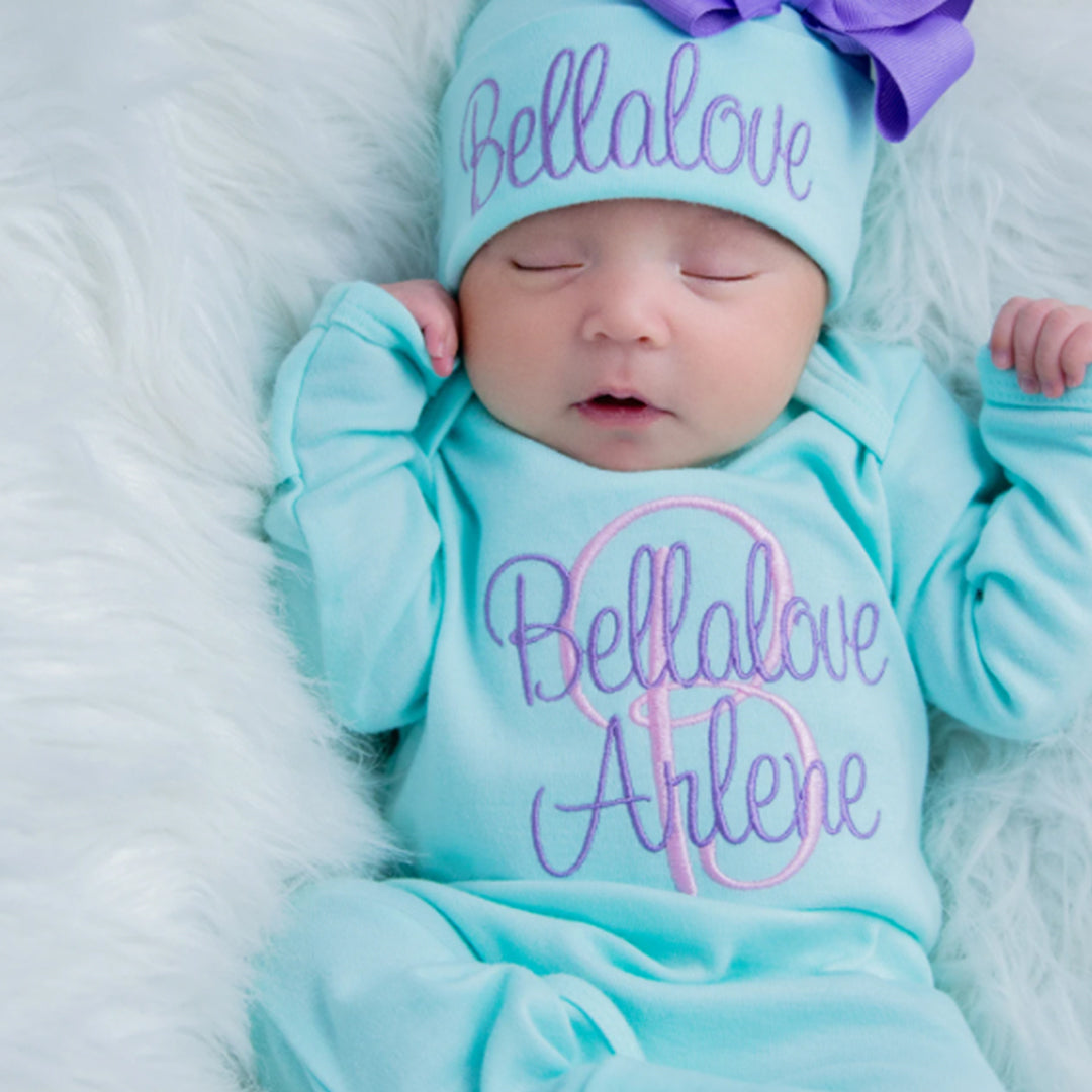 A baby girl wearing the Newborn Girl Personalized Aqua and Purple Hat & Romper Outfit from Junie Grace.