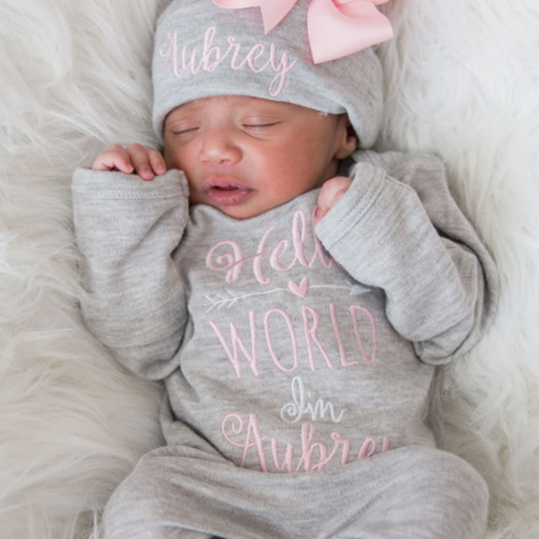 """A baby girl wearing the """"Hello World"""" Personalized Baby Girl Romper Set With Matching Bow Hat from Junie Grace."""