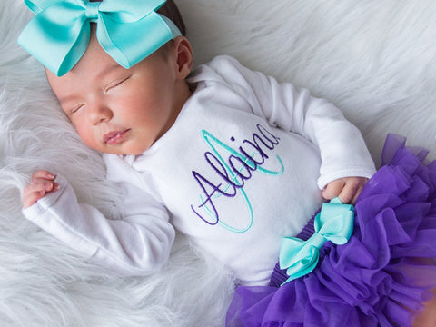 Sleeping baby in purple tutu, personalized top, and blue bow.