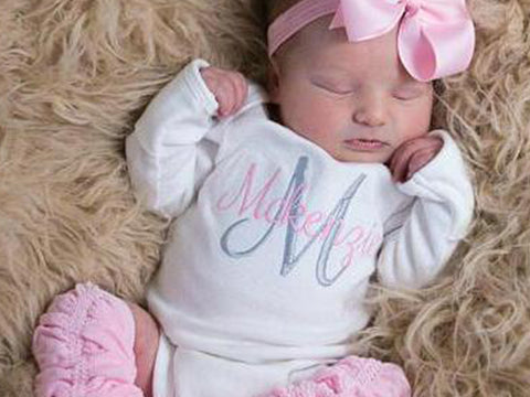 Sleeping baby in personalized outfit with pink leg warmers and bow.