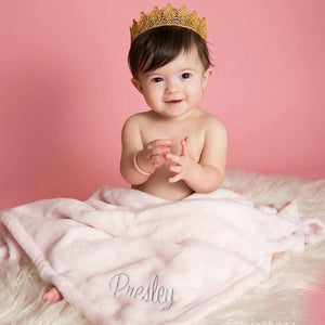little baby girl wearing a crown snuggled in her pink personalized monogrammed blanket with her name Presley