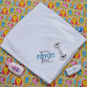 white fluffy baby blanket with monogrammed name in gray and blue