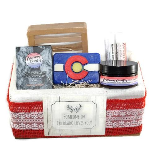 "Beautiful Gift Basket wrapped in Red Burlap and off-white lace.  Basket includes: Colorado Flag Goat Milk Soap, 2 oz. Goat Milk Lotion, Two Refreshing Mint Lip Balms, Goat Milk Face Soap, Soap Dish. Tag on the front says ""Someone in Colorado Loves You."""