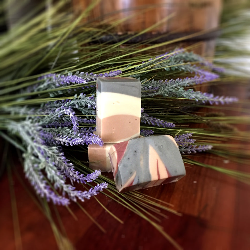Lavender Goat Milk Soap: Beautiful bar with natural colors of pale pink, grey, white, and brick red swirled throughout with whole pieces of Lavender.