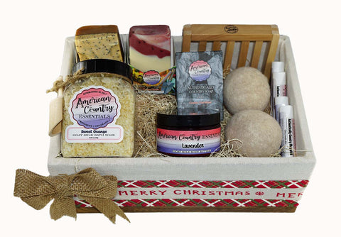 Beautiful Basket decorated with Merry Christmas around the basket and a burlap bow.  The basket is filled with three goat milk soap bars, one goat milk bath soak, one goat milk body butter, two alpaca balls, four natural chapsticks, one wooden soap dish.