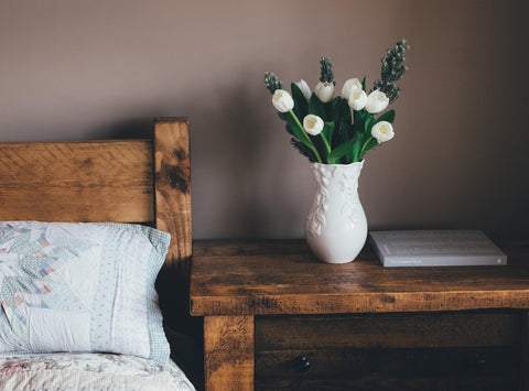 Bedside table with a vase of flowers