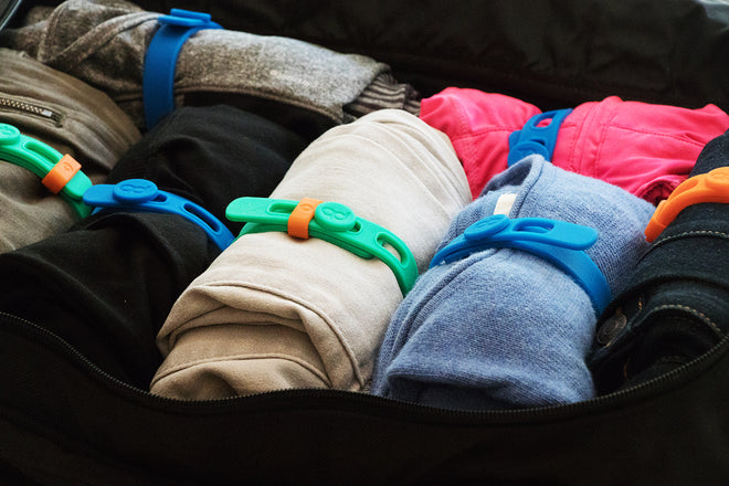 Luggage or backpack with rolled clothing secured with Packbands