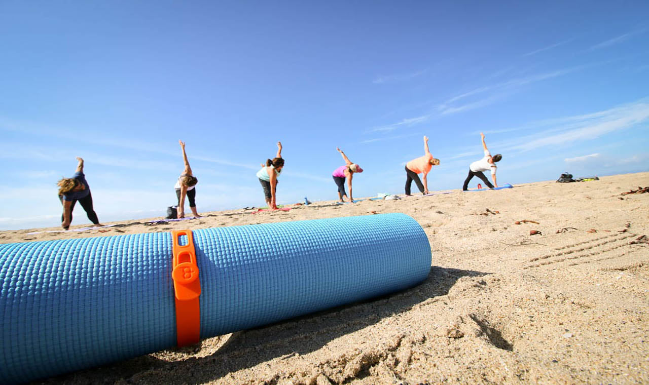 A Packband secures a rolled yoga mat in front of beach yoga