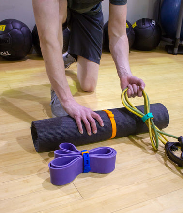 Gym fitness workout equipment including exercise mat, strength bands and jumprope are secured and with Packbands