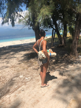 A woman at the beach on vacation using Packbands to hold rolled beach towels