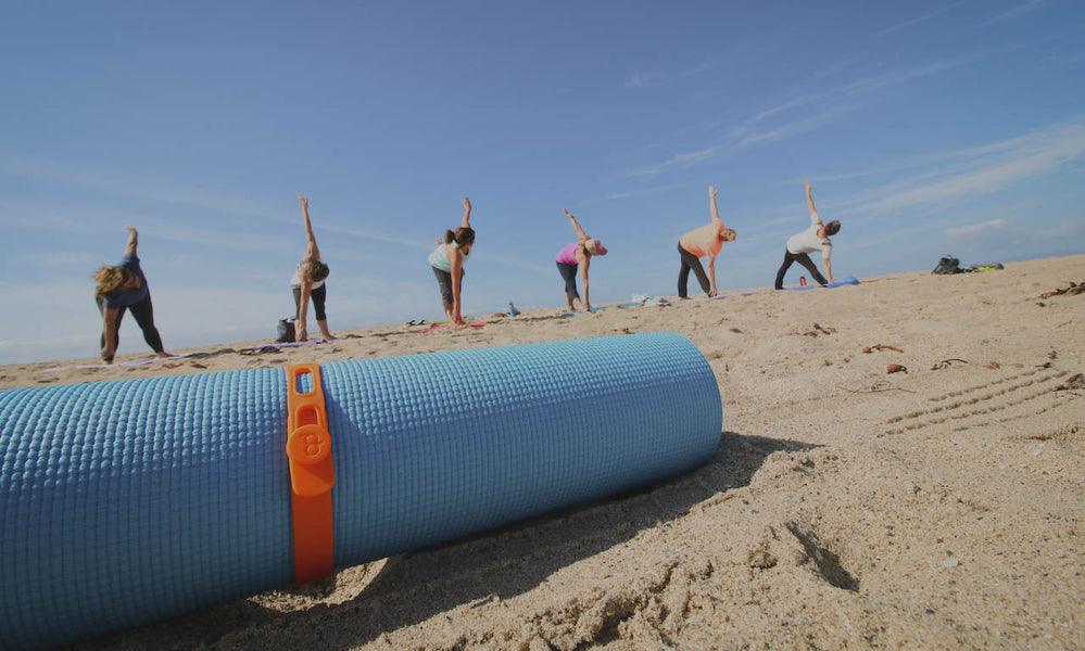 Beach yoga with Packbands strap holding yoga mat