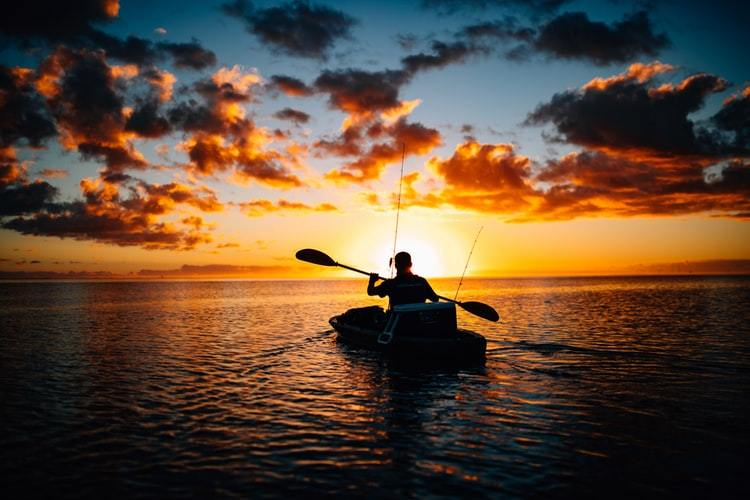 silhouette of man with fishing gear in kayak on water at sunrise