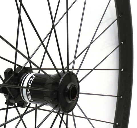 Photo of Specialized Roval 29er wheels rebuilt with Light Bicycle Carbon rims by XLR8 Wheels. Radial right hand side lacing pattern shown on disc front wheel.