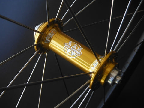 Image of custom alloy road bike wheels using White Industries T11 hubs in Gold and Hplusson Archetype rims in Grey Ano. Front hub shown.