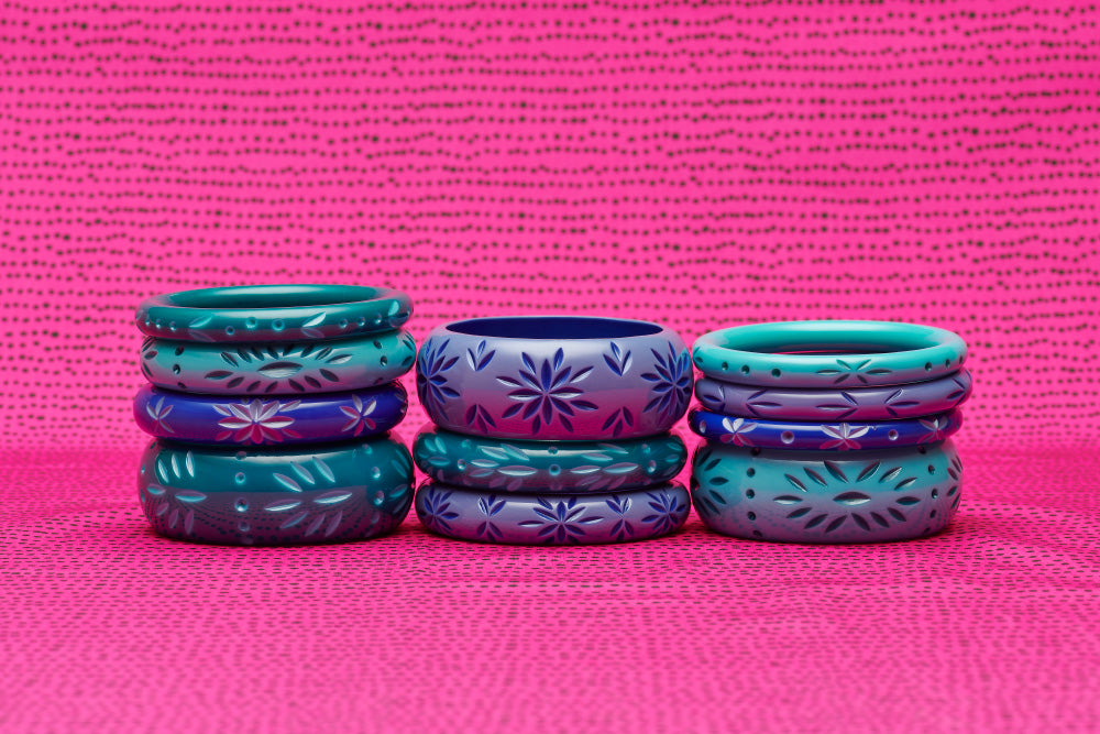 Splendette vintage inspired 1950s carved Duotone fakelite bangle stacks with teal Dragonfly, turquoise Nymph, and blue Cornflower & Forget-Me-Not bangles on bright pink background