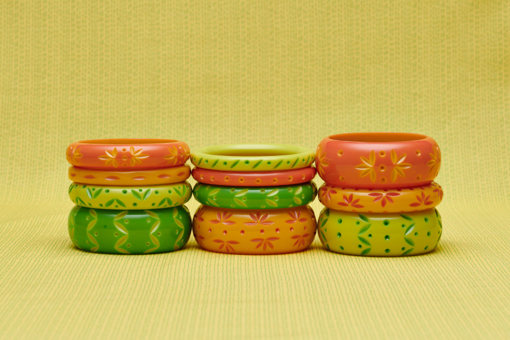 Splendette vintage inspired 1950s style peachy orange, yellow and bright green carved Spring 2021 Duotone fakelite bangles in three stacks. Honeysuckle, Freesia, Lime and Zest