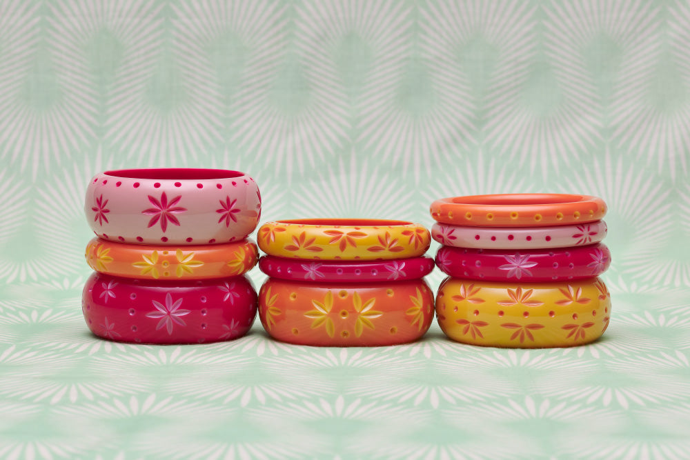 Splendette vintage inspired 1950s pin up style yellow, orange and pink carved Duotone fakelite bangles in three stacks with Ripple, Raspberry, Honeysuckle and Freesia
