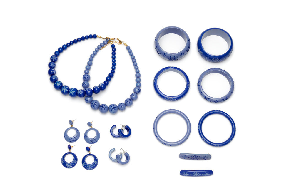 Splendette vintage inspired 1950s style Spring 2021 blue carved Duotone fakelite jewellery flat lay with Cornflower and Forget-Me-Not bangles, bead necklaces, hoop and drop earrings, and hair barrettes