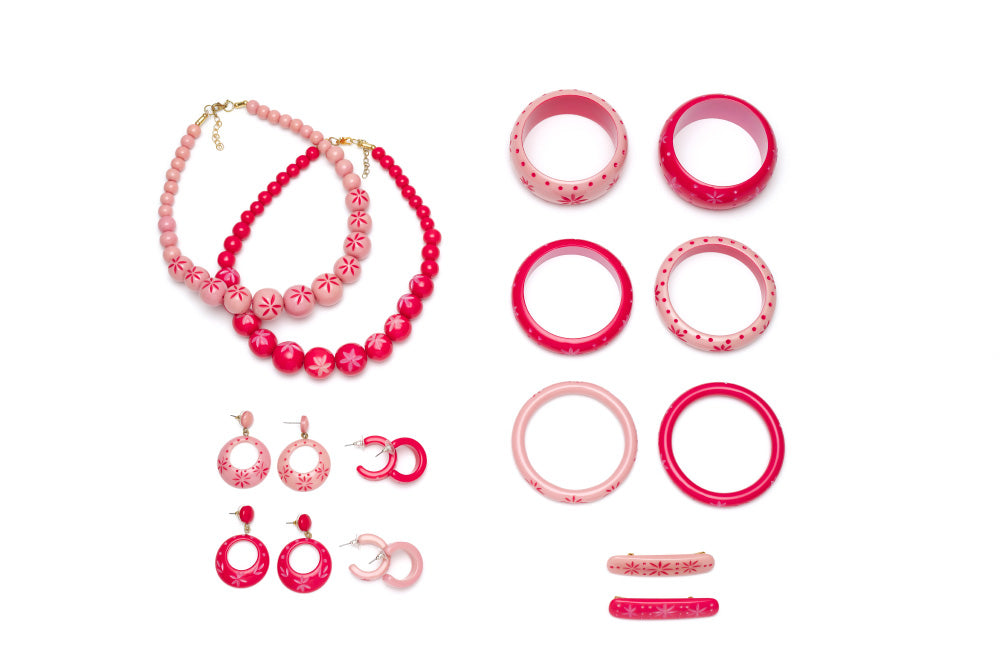 Splendette vintage inspired 1950s pin up style soft pink and bright pink carved Duotone fakelite jewellery flat lay with bangles, earrings, necklaces and hair barrettes