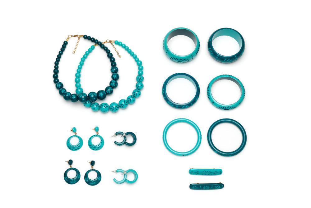 Splendette vintage inspired 1950s tropical style teal and turquoise carved Duotone fakelite jewellery flat lay with bangles, bead necklaces, earrings and hair barrettes