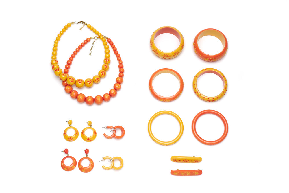 Splendette vintage inspired 1950s Bakelite style peachy orange and yellow carved Duotone fakelite jewellery flat lay with bangles, bead necklaces, earrings and hair barrettes
