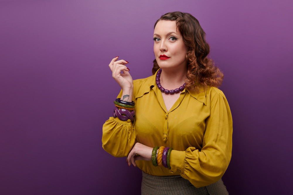 Splendette vintage inspired 1940s Bakelite style Golden Autumn model shot with fakelite jewellery. Plum, Olive and Mustard bangles with Plum necklace