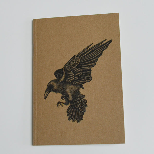 Recycled notebook with raven illustration.