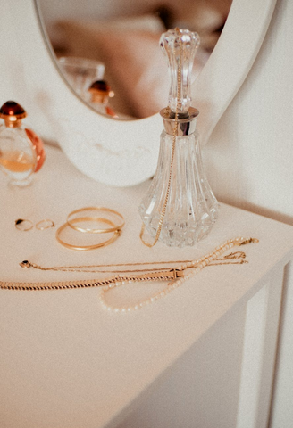 white vanity with glass perfume bottle and gold jewelry